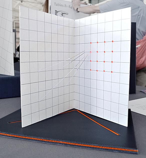 Artists book by Karen Bleitz entitled 78-62 Degrees. Needles suspended by thread pull towards the opposite page.